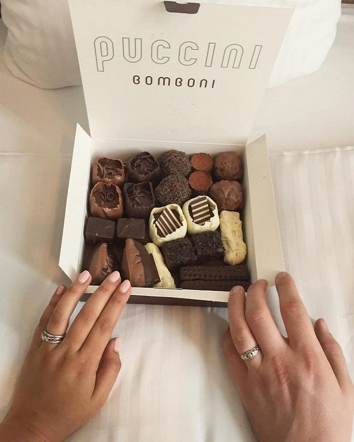 A married couple with a large box of Puccini Bomboni with 2 flavors of each bonbon